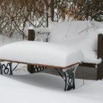 Eine mit Schnee bedeckte Gartenbank und Gartentisch