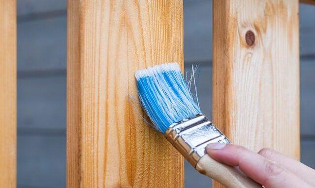 Pinsel streicht einen Holzbalken mit Holzschutzmittel