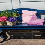 Gartenbank mit Blumen und Kissen dekoriert