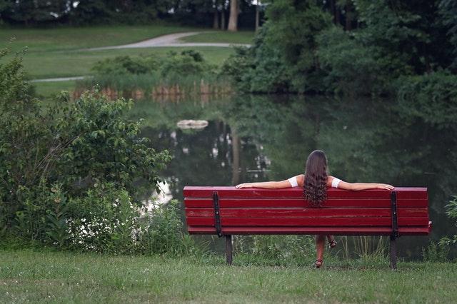 Frau auf Bank am See