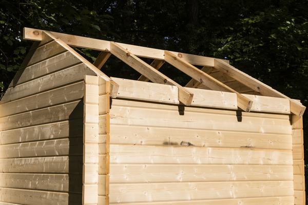 Dach von einer Gartenhütte wird gelegt