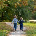 2 Kinder laufen im Garten